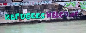 "Graffiti along the Danube reads ""refugees welcome."""