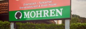 A sign outside a restaurant in Hohenems advertises that they serve Mohren. The beer's name and logo have racial connotations.